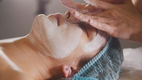 Female doctor performes cosmetic procedure - mask facial massage at spa salon skincare. Close up Royalty Free Stock Photos