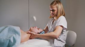 Female doctor performes cosmetic procedure - mask facial massage at spa salon skincare. Close up Stock Photo