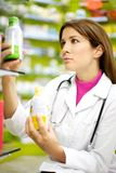 Female doctor in pharmacy looking medicine Royalty Free Stock Photo