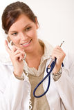 Female doctor on the phone. Happy female doctor on the phone  with stethoscope Royalty Free Stock Photos