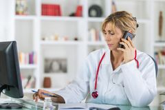 Female doctor on phone at office with computer stock photos