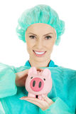 Female doctor with pink piggy bank. Stock Images