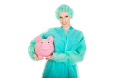 Female doctor with pink piggy bank. Stock Image