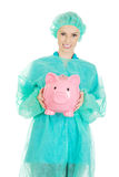 Female doctor with pink piggy bank. Stock Photo