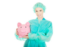 Female doctor with pink piggy bank. Royalty Free Stock Images
