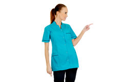 Female doctor pointing aside. Royalty Free Stock Photos