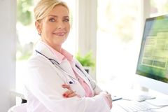 Female doctor portrait at the medical room. Beautiful smiling female research physician sitting in front of her computer at the doctor`s office and working royalty free stock images