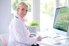 Female doctor portrait at the medical room. Beautiful smiling female research physician sitting in front of her computer at the doctor`s office and working stock image