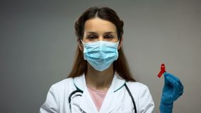 Female doctor in protective mask showing red ribbon, low immunity, HIV AIDS royalty free stock photos