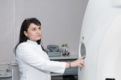 A female doctor pushing control button on CT scanner royalty free stock photography