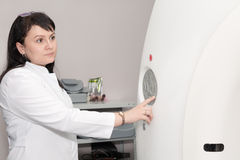 A female doctor pushing control button on CT scanner Stock Photography