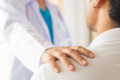 Female doctor put hand on patient shoulder for encouragement. And discussion. Medicine and health care concept. Doctor and patient royalty free stock photography