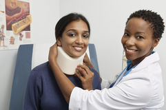 Female Doctor Putting Brace On Patient's Neck Stock Photography