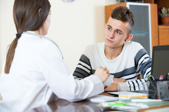 Female doctor questioning teen patient at office Royalty Free Stock Photography