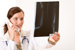 Female doctor with x-ray and phone Royalty Free Stock Image