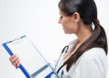 Female doctor reading notes on clipboard Royalty Free Stock Image