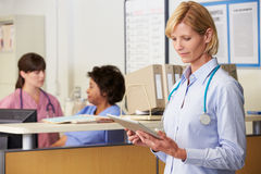 Female Doctor Reading Patient Notes At Nurses Station Stock Image