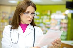 Female doctor reading prescription in pharmacy Stock Images