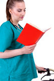 Female doctor reading red book Stock Photography