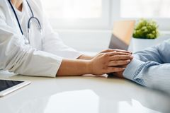 Female doctor reassuring the patient and holding his hands royalty free stock photos