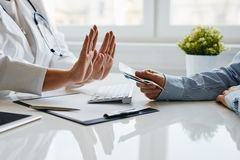 A female doctor refuses a bribe from her patient stock photos