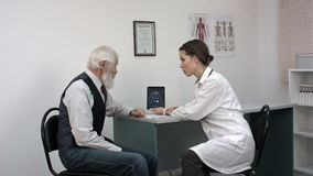 Female doctor reviewing x-ray on a tablet with mature patient. stock footage