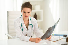 Female doctor with roentgen sitting at desk in office. Modern health care. Portrait of female doctor with roentgen sitting at a desk in the office Royalty Free Stock Image