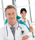 Female doctor in a row smiling at the camera. Attractive female doctor in a row smiling at the camera Royalty Free Stock Photos