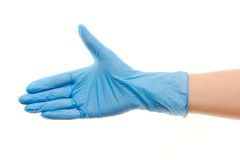 Female doctor's hand in blue surgical glove giving for handshake. Close up of female doctor's hand in blue sterilized surgical glove giving for handshake against Royalty Free Stock Photos