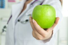 Female doctor's hand giving fresh green apple Royalty Free Stock Image