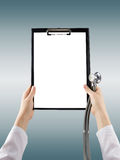 Female doctor's hand holding blank medical clipboard and stethos. Cope on blurred background. Concept of Healthcare And Medicine. Copy space Royalty Free Stock Photography