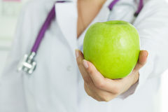 Female doctor's hand holding fresh green apple. Healthcare and medical concept. Copy space Stock Photos