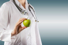 Female doctor's hand holding green apple. Close up shot on grey Stock Images