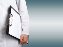 Female doctor's hand holding medical clipboard with blank sheet. Of paper on blurred background. Concept of Healthcare And Medicine. Copy space Royalty Free Stock Photo
