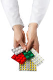 Female doctor's hand holding medical pills isolated on white bac Stock Photo