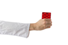 Female doctor's hand holding medical pills isolated on white background. First aid Royalty Free Stock Image