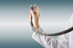 Female doctor's hand holding stethoscope on blurred background. Stock Photography