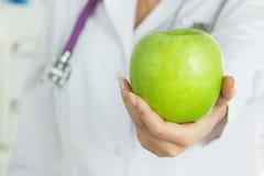 Female doctor's hand offering fresh green apple Stock Image