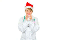 Female doctor in Santa hat enjoying cup of hot cof Royalty Free Stock Photography