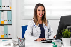 Female doctor sat at desk using computer stock photos