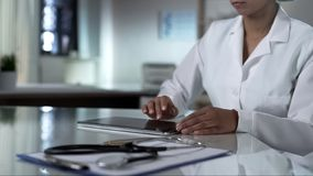 Female doctor scrolling tablet screen, checking patients test results, clinic royalty free stock image