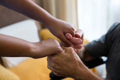 Female doctor and senior man holding hands in nursing home. Cropped image of female doctor and senior men holding hands in nursing home royalty free stock photos