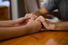 Female doctor and senior man holding hands at table Royalty Free Stock Image