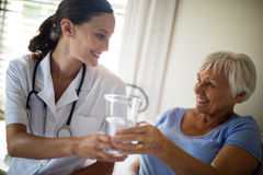 Female doctor serving a water glass to senior woman in the bedroom Royalty Free Stock Image