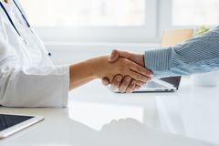 Female doctor shakes hands with his patient. In medical office stock images