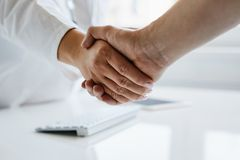 Female doctor shakes hands with his patient stock photo