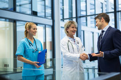 Female doctor shaking hands with businessman stock photos