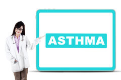 Female doctor showing asthma word on a board. Picture of female doctor showing a word of asthma on the billboard while standing in the studio Royalty Free Stock Image