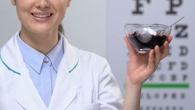 Female doctor showing bilberry at camera against eye chart, vision health care. Stock footage stock video