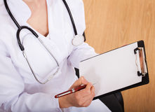 Female doctor showing blank clipboard Stock Image